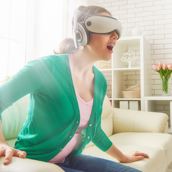 Beautiful young woman playing game in virtual reality glasses.